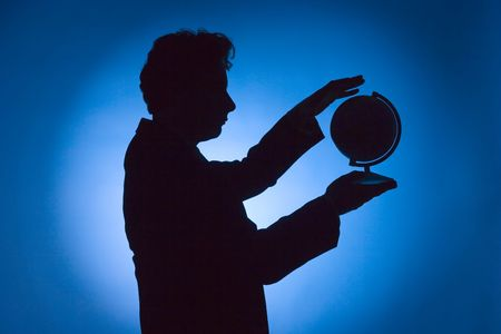 silhouette of man with globe on blue background