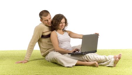 isolated on white young couple on green carpet with laptop