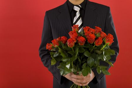 Businessman with bouquet of roses in hands. We don't see his face. Front view