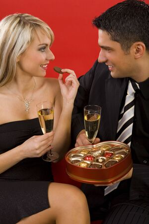 Young, sitting couple with glass of champagne in hands. They are smiling and looking at each other. Man is holding box of chocolates, woman is eating one