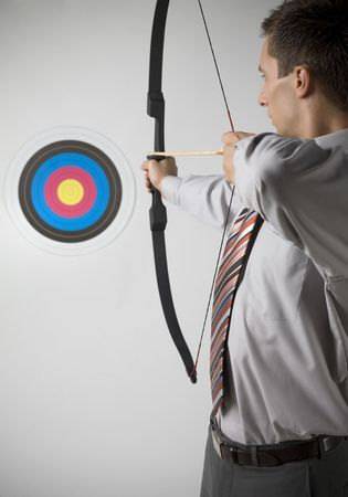 Businessman holding bow and shooting to archery target. Rear view, gray background