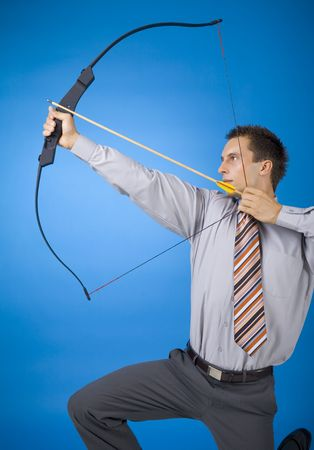 Young businessman holding bow and shooting to target. Blue background