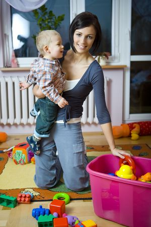 Young woman with  boy during plaing. Woman holding  on hand taking toy from container. Front view.