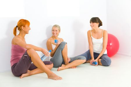 Group of women dressed sportswear sitting on the floor. They holding water bottles and talking.