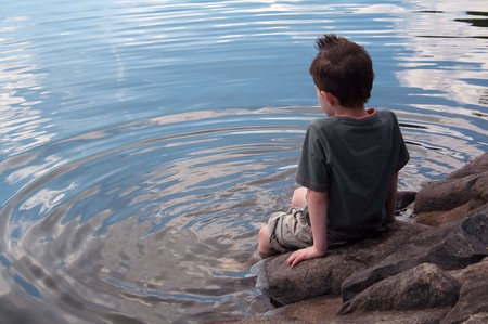 Lonely boy in thought paddles feet in lake with copy space left