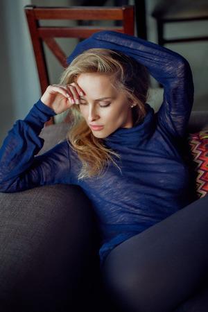 fashion portrait of young blonde elegant woman sitting in sofa
