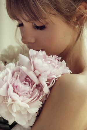 Photo for Beautiful girl holding white and rose peonies, attractive woman with big bouquet, female smells flowers, studio with sunlight. - Royalty Free Image
