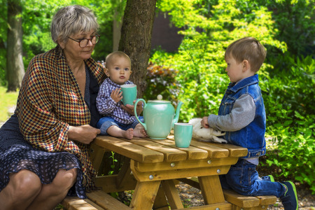Grandmother having tea with her grandchildren