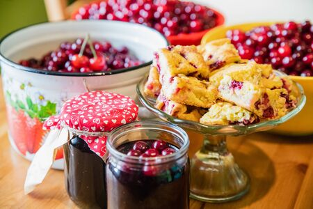 Photo pour Jars of tasty summer cherry jam with baked cherry cake and raw cherries background - image libre de droit