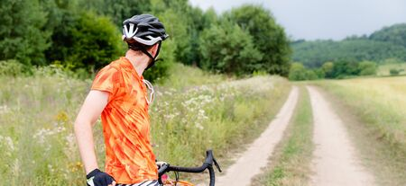 Photo pour Man with bicycle in full cycling equipment with helmet, orange t-shirt in green summer field looking at road, active healthy lifestyle in nature envirment banner copy space - image libre de droit