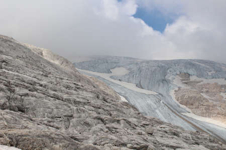 Glacier tongue in the Alps next to rocky ground and cloudy sky in the background