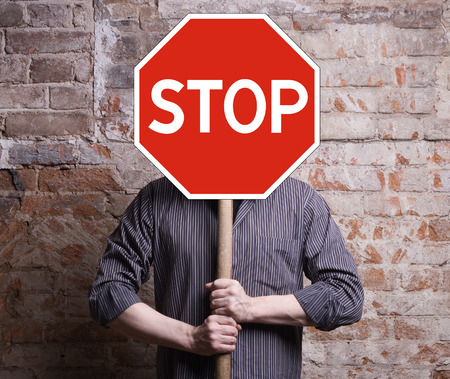Photo pour A man holds a sign forbidding face. - image libre de droit