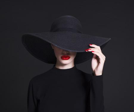 Foto de Luxury woman in a large black hat and bright lips on black background - Imagen libre de derechos