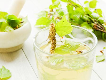 Photo pour Birch tree sap drink and leaves on white wooden - image libre de droit