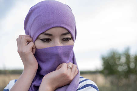 Photo for The Muslim woman in the headscarf looked down modestly. A married Muslim woman in a headscarf. A woman in a hijab with only her eyes visible. - Royalty Free Image