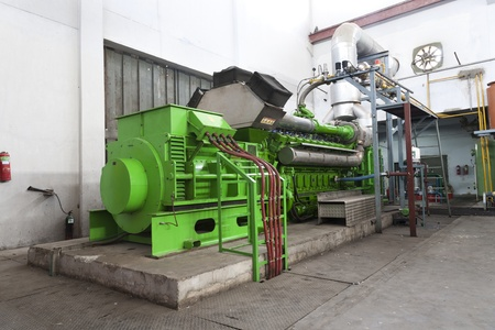 huge industrial standby dieasel generator at a power generation plant in a textile factory.