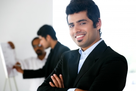 close up of a confident businessman with his colleagues in the background