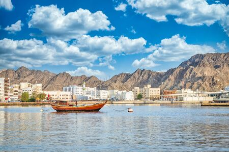 Photo pour Old Sailboat anchored at Muttrah Corniche. The the old city and mountains in the background. From Muscat, Oman. - image libre de droit