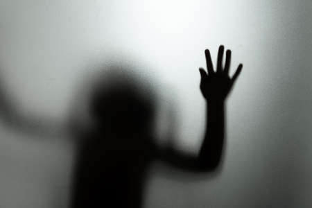 Photo for Ghost concept shadow of a child behind the matte glass blurry hand and body soft focus - Royalty Free Image