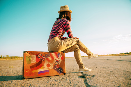Traveler woman sits on retro suitcase and looks away on road. Suitcase with stamps flags representing each country traveled.