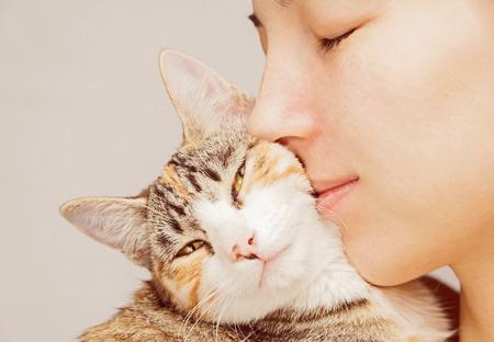 Happy woman is hugging orange tabby feline