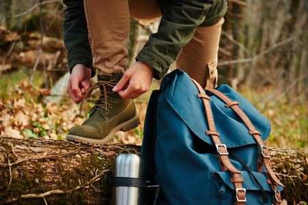 Female hiker tying shoelaces outdoors in autumn forest, near thermos and backpack. View of legs. Hiking and leisure theme