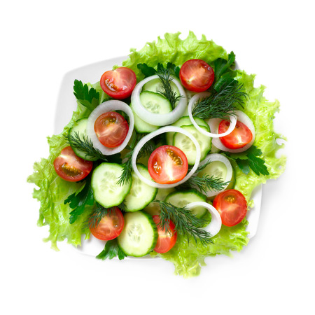 Salad of cucumbers, tomatoes and greens on a white background, top view
