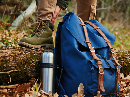 Female hiker wears boots outdoors in autumn forest, near thermos and backpack. View of legs. Hiking and leisure theme