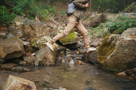 Hiker woman crossing a creek on stones in summer forest, view of legs