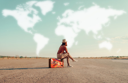 Foto de Traveler woman sitting on a suitcase and dreaming about adventures. Map of the world is painted in sky. Concept of travel - Imagen libre de derechos
