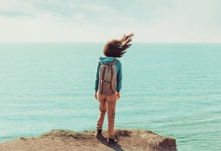 Traveler young woman with backpack standing on coastline near the sea in windy weather, her hair fluttering in the wind