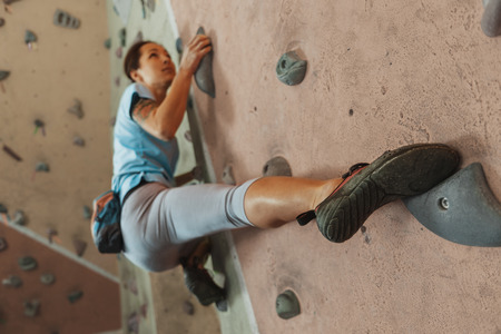 Free climber young woman climbing on practical wall indoor, bouldering