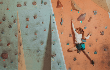 Sporty little girl climbing artificial boulder on practical wall in gym