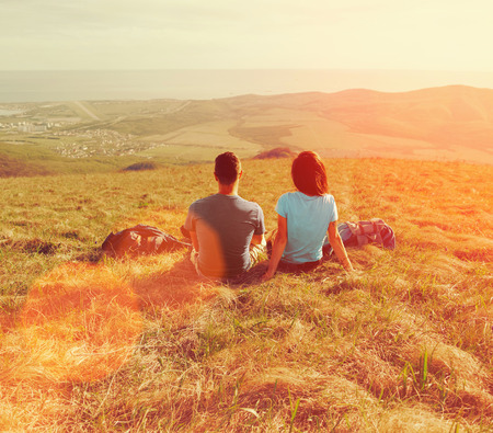 Loving couple sitting on mountain meadow and enjoying view of nature at sunny day in summer