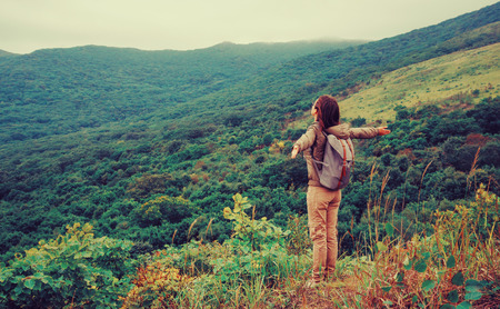 Freedom happy traveler woman standing with raised arms and enjoying a beautiful nature. Image with instagram color effect