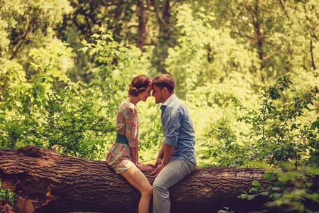 Young loving couple sitting on fallen trunk tree in summer park, tender scene