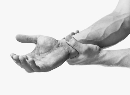 Pain in a male wrist. Man holds his hand, close-up image. Monochrome image, isolated on a white background