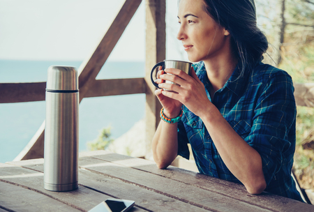 Young woman resting in wooden veranda in summer outdoor. Girl drinking tea in arbor