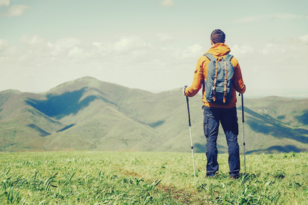 Hiker young man with backpack and trekking poles looking at mountains in summer outdoor. Free space in left part of the image