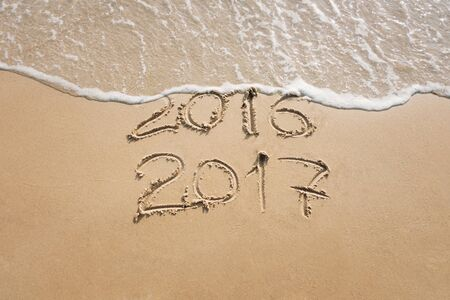 Photo pour Old year 2016 and new year 2017 written on sand near the sea, wave washes away 2016 - image libre de droit