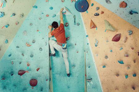Photo pour Free climber young man climbing artificial boulder indoors - image libre de droit