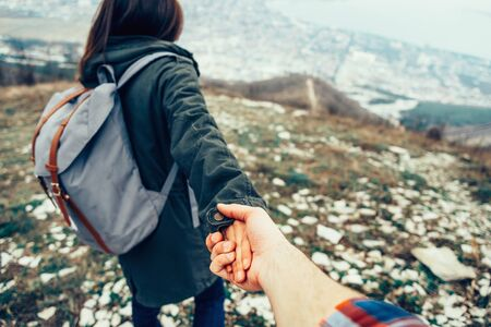 Photo pour Hiker young woman holding man's hand and leading him on nature outdoor. Couple in love. Focus on hands. - image libre de droit