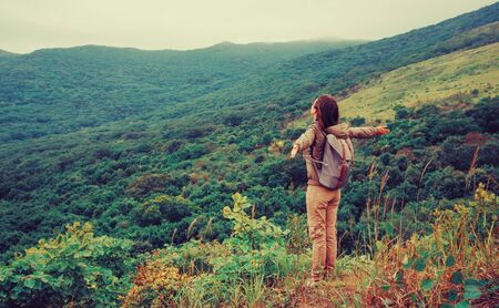 Photo pour Freedom happy traveler woman standing with raised arms and enjoying a beautiful nature. - image libre de droit
