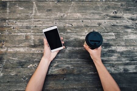 Photo for Point of view of female hands holding smartphone and takeaway cup of coffee on wooden background, mock-up. - Royalty Free Image