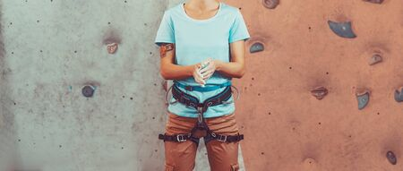 Photo pour Climber young woman coating her hands in powder chalk magnesium and preparing to climb indoor - image libre de droit