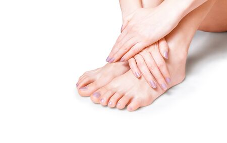 Photo for Beautiful female hands grasping feet on the white background - Royalty Free Image