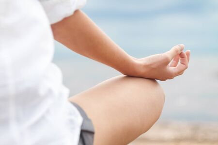 Photo for Woman meditating in lotus position on beach, closeup part of body - Royalty Free Image