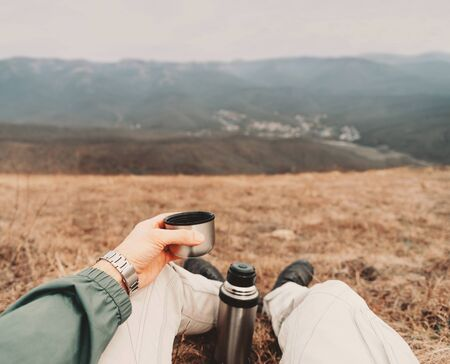 Photo for Traveler man sitting with cup of tea and flask in the mountains. Point of view shot - Royalty Free Image