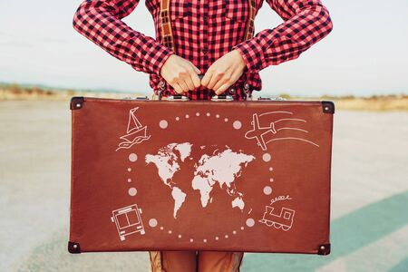 Foto de Traveler woman standing with a suitcase. Map of the world and types of transport are painted on suitcase. Concept of travel - Imagen libre de derechos
