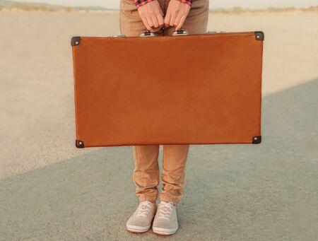 Photo pour Traveler holding a suitcase, view of hands. Space for text on suitcase - image libre de droit